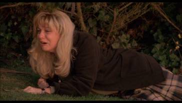 Laura Palmer lies on grass crying