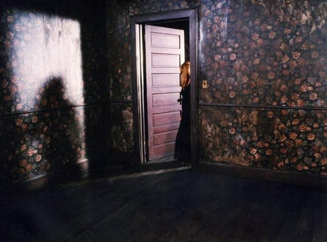 Laura Palmer stands in a door way to the convenience store which has flowery wallpaper
