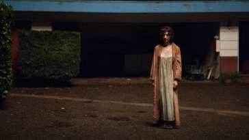 a strange androgynous person wearing a nightgown and robe outside a motel