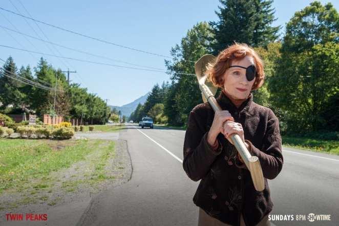 Nadine walks down a road carrying a golden shovel over her shoulder