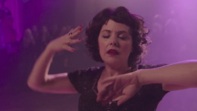 Audrey Horne dances with her eyes closed, bathed in purple light