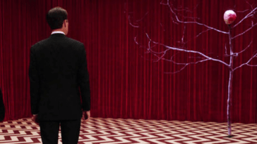 Philip Gerard and Dale Cooper look on to a tree-like creature. The floor is chevron patterned and the wall is a red curtain.