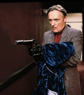 Frank Booth holds a gown of blue velvet as he holds up a gun