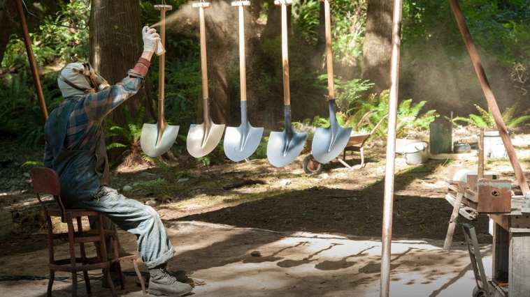 Jacoby, wearing a gasmask, spraypaints shovels that are hanging on a rack outside in the woods.