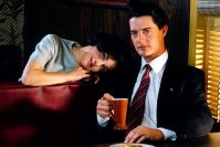 audrey horne rests her head on dale coopers shoulder while he drinks coffee in a booth