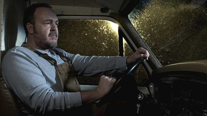 Brent Sexton as Stan Larsen sits in the front of his van in the dark and rain in The Killing