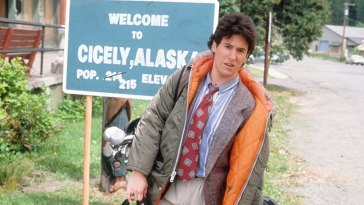 Joel stands at the Cicely town welcome sign