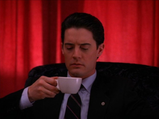 Cooper holding a cup of coffee in the red room