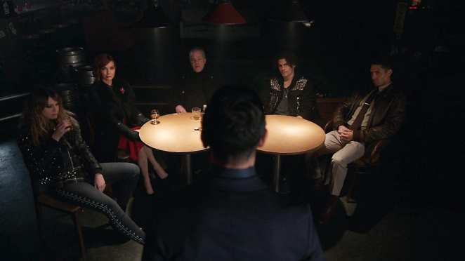 a group of people sit around a table while a man stands and talks in front of them