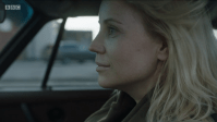 a blonde woman sits in her car staring ahead with a slight smile