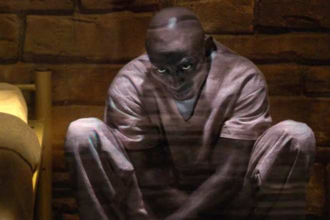 A hologram of Clayton Leigh squats in a cell