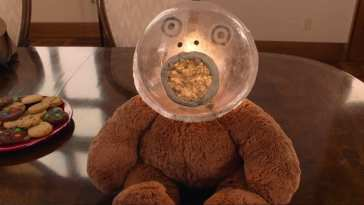 A stuffed bear has a translucent sphere with a face drawn on it for a head