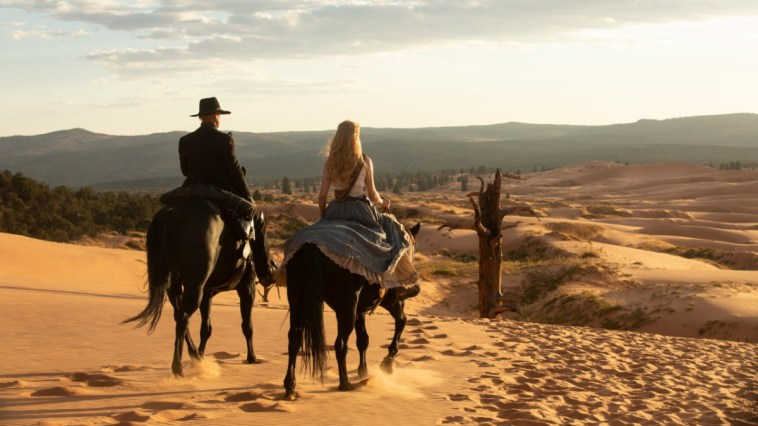 The Man in Black and Dolores are riding horses and overlooking a valley