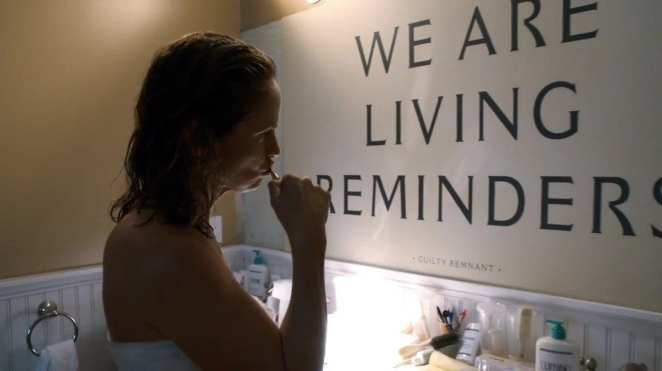 """Laurie brushes her teeth in front of a sign that reads """"We are living reminders"""""""