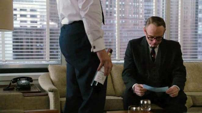 Lane reads a note while sitting on the office sofa, Don stands in front of him with a bottle of whiskey