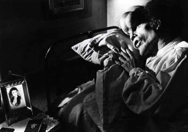 the Elephant man lies on a pillow looking at a photograph of a woman