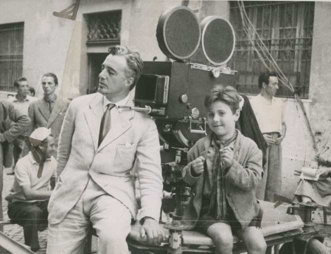 a man and a boy sit by a film camera in Bicycle Thieves