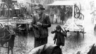 Bruno and Antonio in an italian market place in the pouring rain
