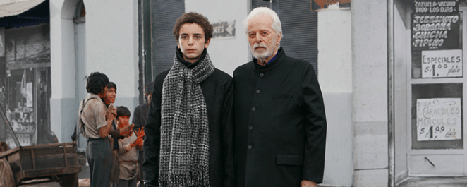 A young man and an old man stand next to each other outside a shop