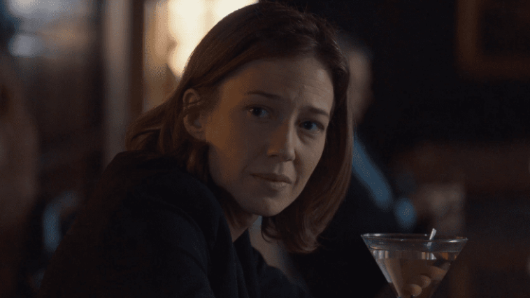 Nora Durst looks down the bar with a martini in front of her