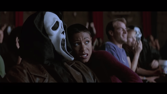 a man in the scream mask with his girlfriend in the cinema frightened by a scary movie
