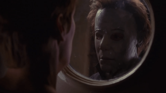 Michael Myers looks at his masked face in a mirror