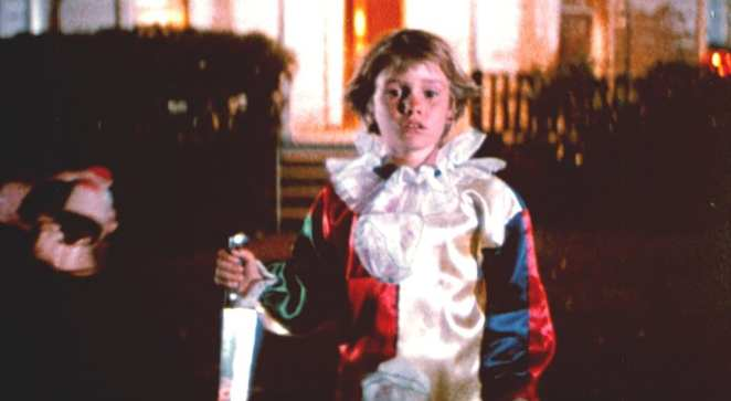 a boy dressed as a clown brandishes a large knife