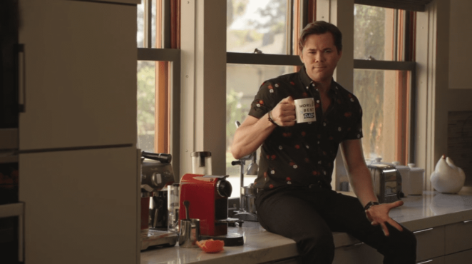 """David Patton (Andrew Rannells) drinks from Alex Myers' (Ron Livingston) World's Best Dad mug while talking to him The Romanoffs """"Bright and High Circle"""""""