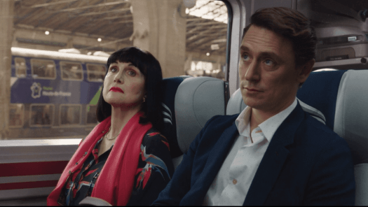 a man and woman sit on a train attentive to the conductor's announcement adele anderson jj feild candace jack the romanoffs