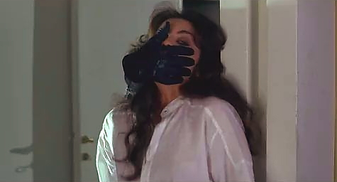 a woman in a white shirt is surprised by a leather gloved hand covers her mouth
