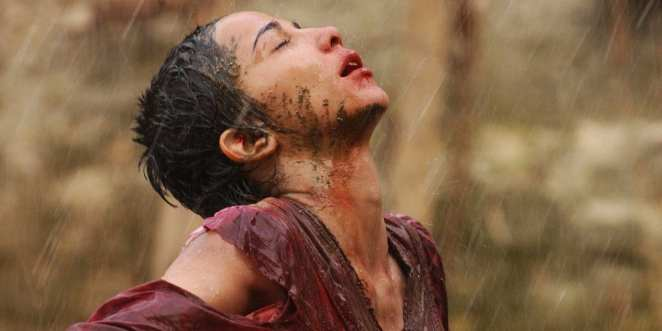 A girl, muddy and wet stands raising her face to the rain