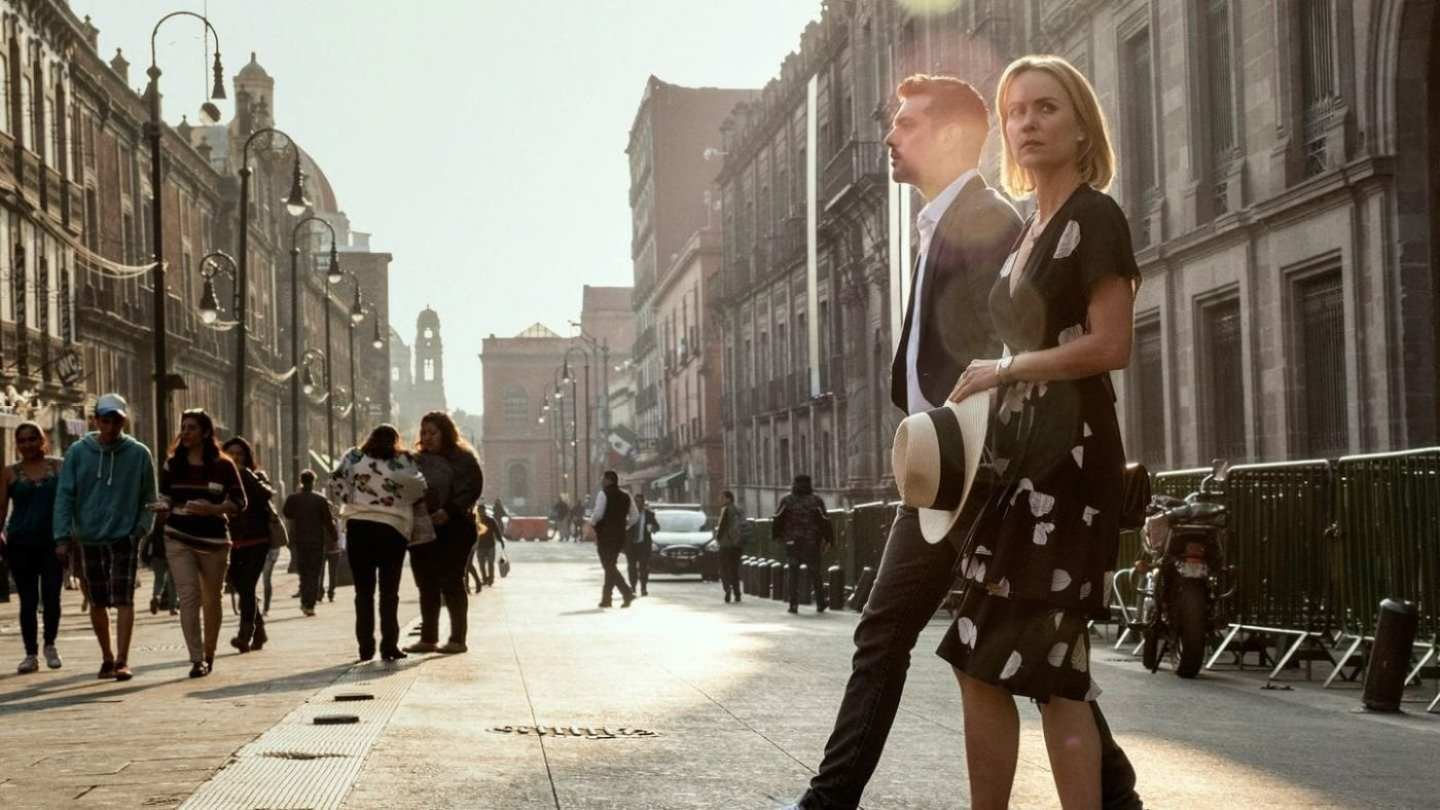 a man and a woman walk across a street in sunshine