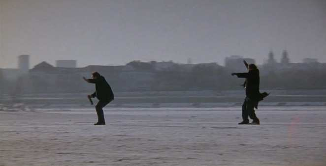 2 men on a beach in strong winds in Three Colors: White