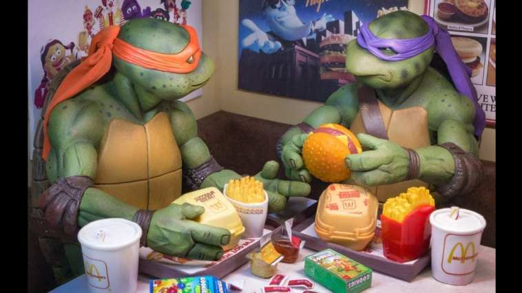 two animorphic turtles eat various fast food items at a table