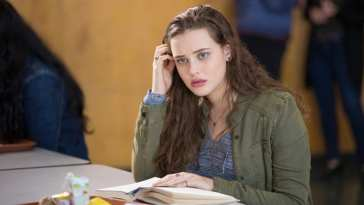 Hannah Baker (Katherine Langford) sits at a table with a book in 13 Reasons Why