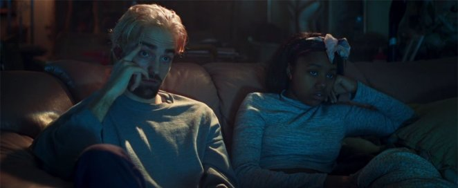 While taking shelter in a stranger's home, Connie (Robert Pattinson) sits with Crystal (Taliah Webster).