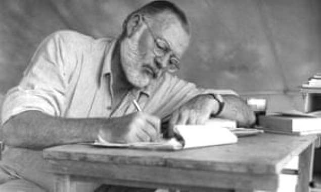 A man with a beard and glasses writes at a table