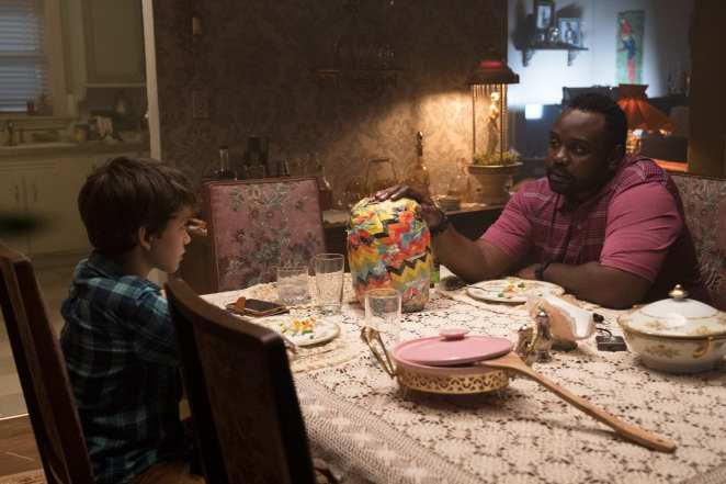 """Detective Mke Norris (Brian Tyree-Henry) and Andy (Gabriel Bateman) talk over dinner, a strange """"gift"""" in between them."""