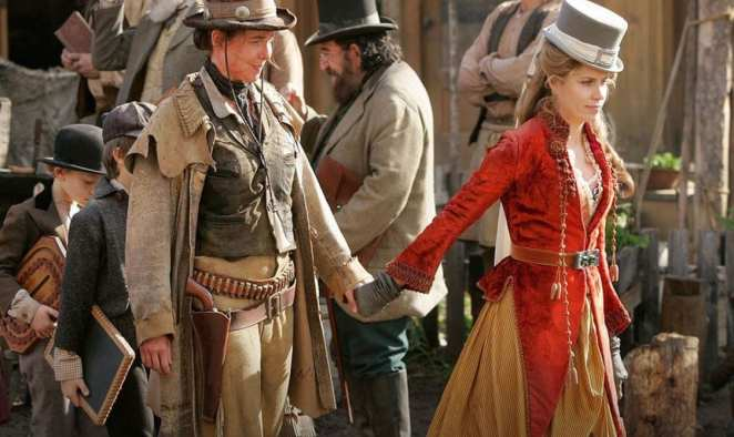 Jane holds hands with Joanie Stubbs while escorting children through the streets of Deadwood
