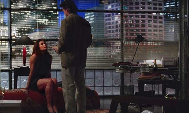Demi Moore seated on a sofa looking up at Michael Douglas in an office