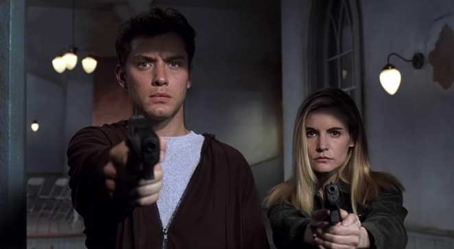 Jude Law and Jennifer Jason Leigh holding guns in the final scene of eXistenZ.