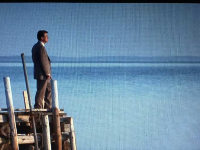 Giles stands on a pier, looking out over the ocean