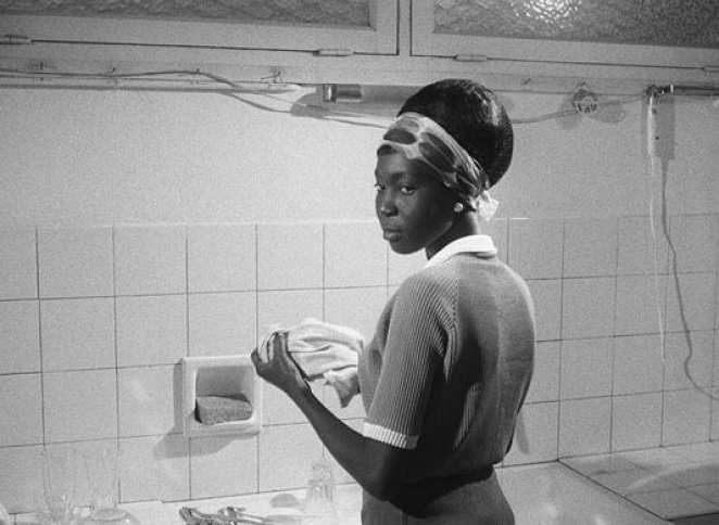 A Black woman stands at a sink washing dishes