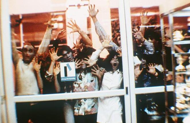 Zombies pressed against the glass door from the original Dawn of the Dead
