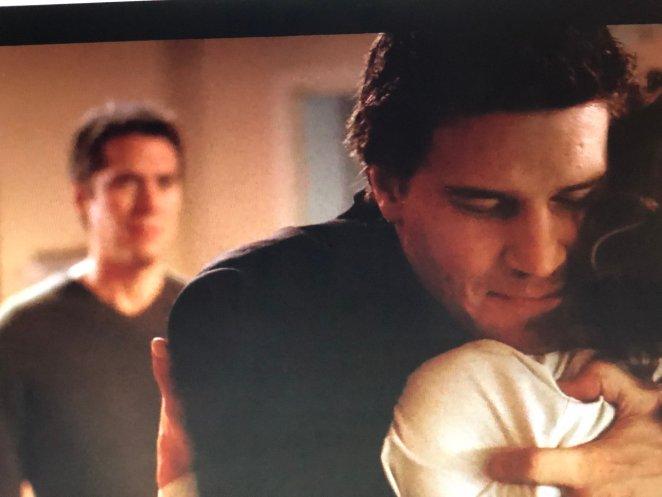 Angel embraces newly-awakened Cordelia, while Wesley looks on.