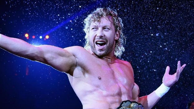 The wrestler Kenny Omega stretches his hand out in a gun shape, in his signature 'goodbye and goodnight' pose