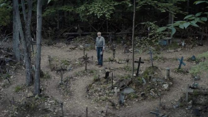 man stands alone in graveyard full of crosses