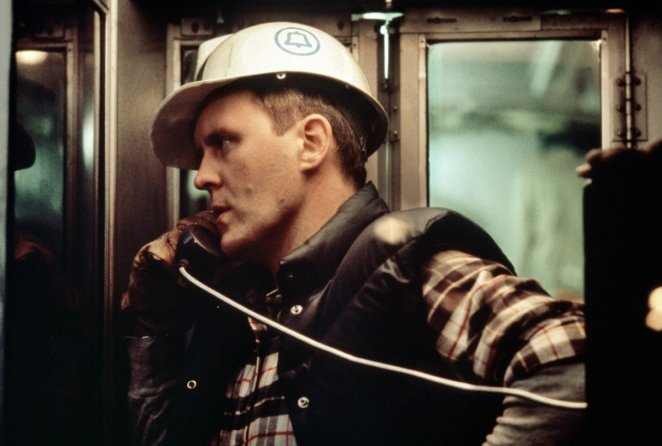 Burk (John Lithgow) wearing a hard hat and talking on a telephone in Blow Out