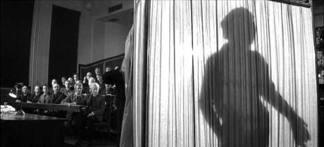An audience looks on as the the silhouette of John Merrick looms on a curtain