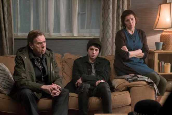 Ed, Mary and Sam sit on a sofa looking pensive